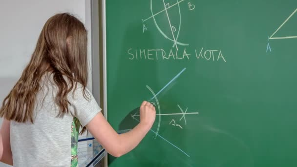 The students are having a Maths class. This particular student is standing in front of the blackboard and she draws a line and uses a chalk and a ruler.