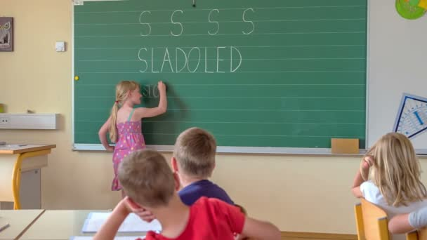 A first-grade student is writing another word beginning with an s on the blackboard.