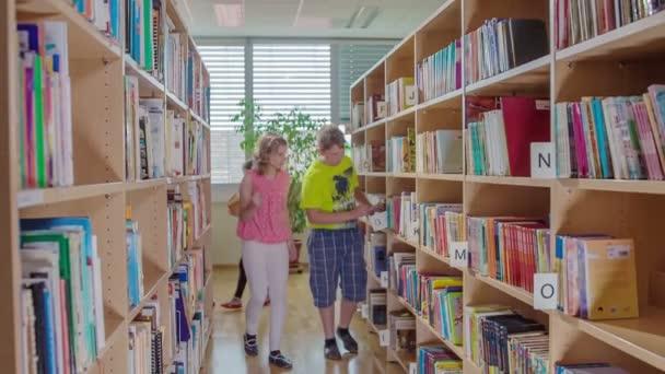 Dva studenti hledají určitou knihu v knihovně a pak ji najdou.