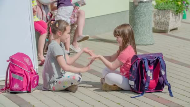 Two girls are sitting on the ground outside of school and are playing a game where they are clapping with their hands.
