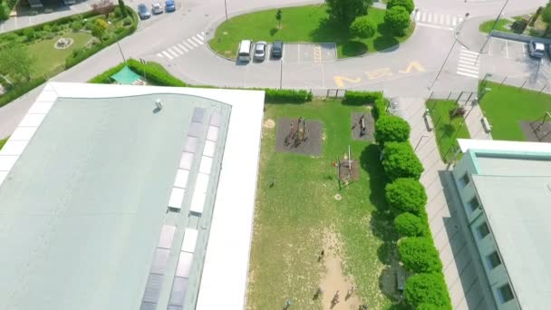 Children are gathered outside the school. Its a warm day. Aerial shot.