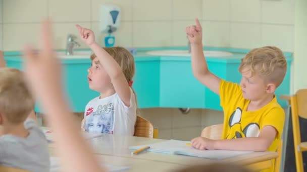 Students are raising their hands up in the air because they know the answer that their teacher is asking them.