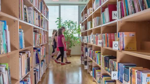 Young girls are in a library and they are getting new books and are learning new things.