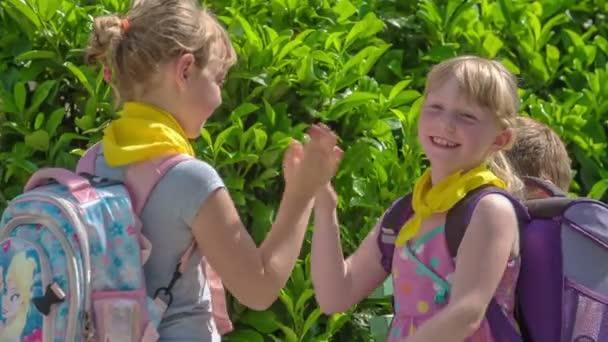 Dva studenti v první třídě tleskají. Hrají hru mimo školu na hřišti.