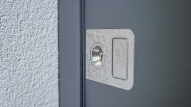 A man pushes a button next to a lock on the front door.