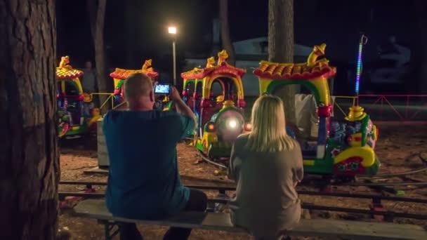 Egy színes vonat halad a síneken a vidámparkban.