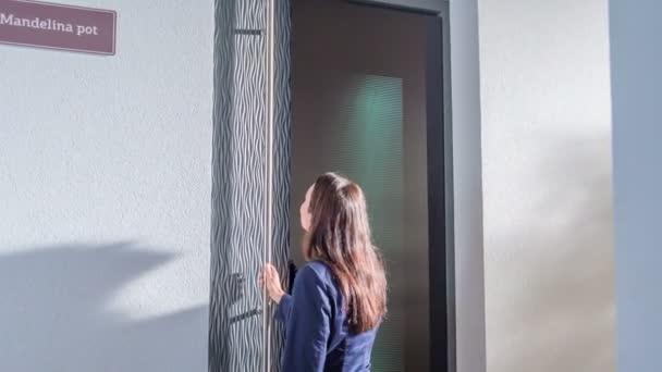 Eine Geschäftsfrau kommt und berührt die Eingangstür zu einem Haus. Dann drückt sie einen Knopf, die Haustür öffnet sich und sie geht in ein Haus.