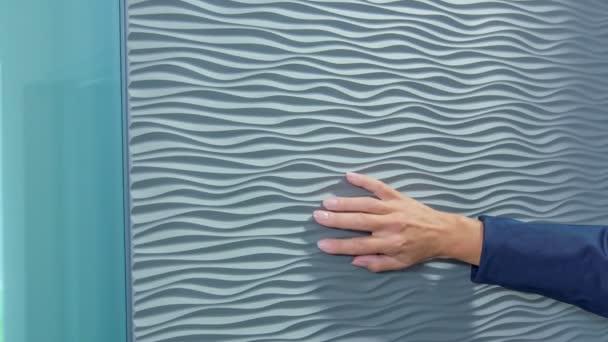 Eine Frau bewegt langsam ihre Hand auf der Oberfläche der Haustür. Sie will sehen, wie das Material ist.