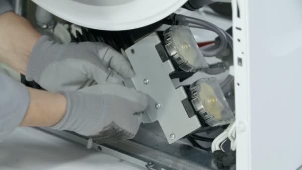 Reparaturarbeiter bereitet sich darauf vor, eine kleine Schraube von der Metallplatte abzuschrauben, die wichtige elektrische Teile der Waschmaschine hält.