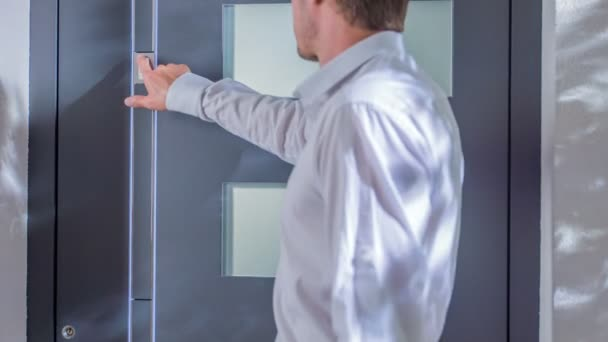 Muž tlačí na knoflík. Otevře přední dveře a pak projde skrz.