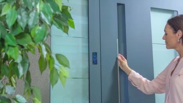 eine Frau gibt einen Code aus vier Zahlen ein, bevor sie das Haus betritt.