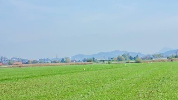 Ein Flugzeug landet auf einem Gras, das auf diesem kleinen Privatflughafen als Landebahn dient. es ist ein schöner sonniger Tag.