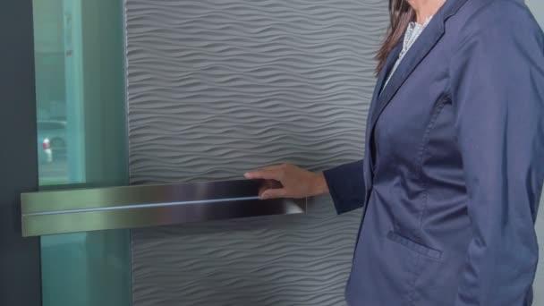 Eine Frau berührt die graue Oberfläche der Haustür und einen Griff. sie beobachtet sorgfältig die Haustür.