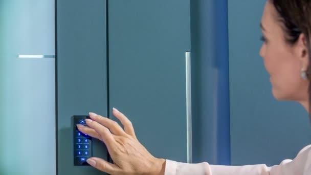 eine Frau mittleren Alters drückt einen Code, um die Haustür aufzuschließen. dann geht sie ins Haus.