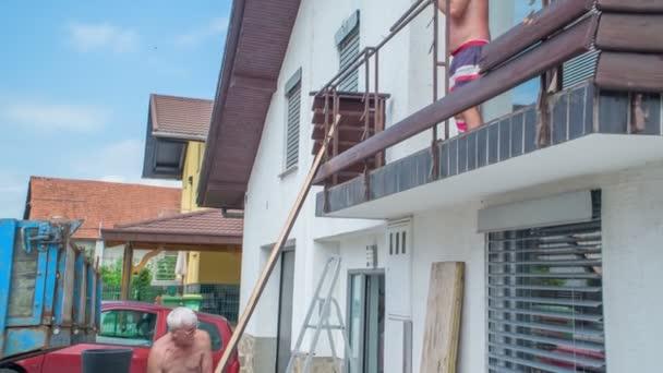 Starší muži odstraňují prkno z pevné balkonové konstrukce. Jeden tahá prkno a druhý ho odstraňuje pomocí válečné sekery..