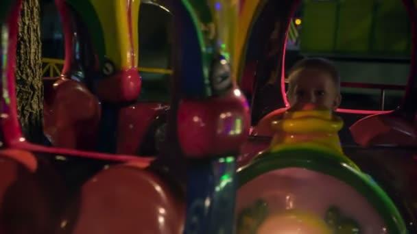 Gyerekek vezetnek a színes vonaton a vidámparkban.