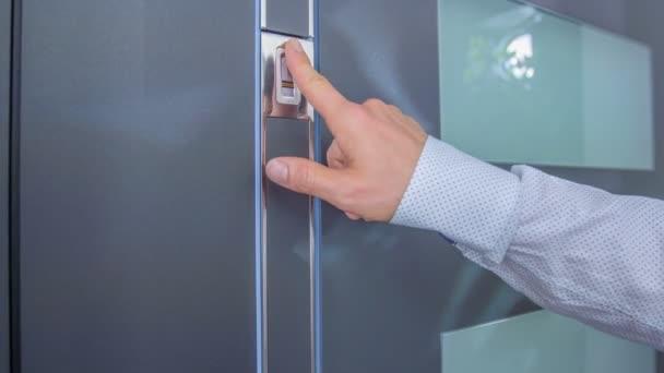 ein Geschäftsmann drückt den Knopf an der Eingangstür.