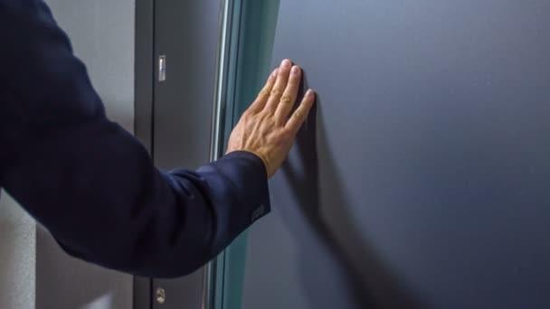 Ein Mann berührt das Äußere und den Griff an der Tür sehr sanft.