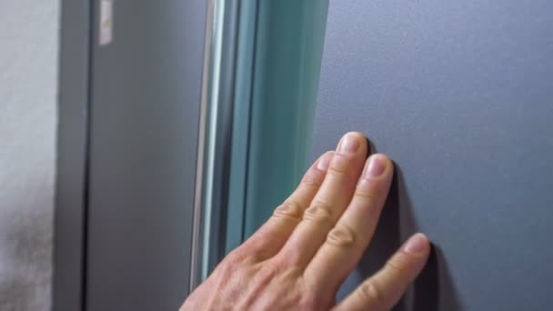 A businessman is touching the exterior of the front door very gently. He also touches the handle.