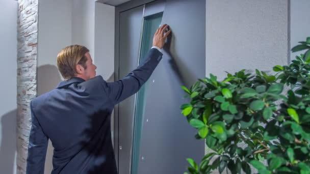 Ein Mann kontrolliert das Äußere der Haustür sehr sanft mit der Hand.