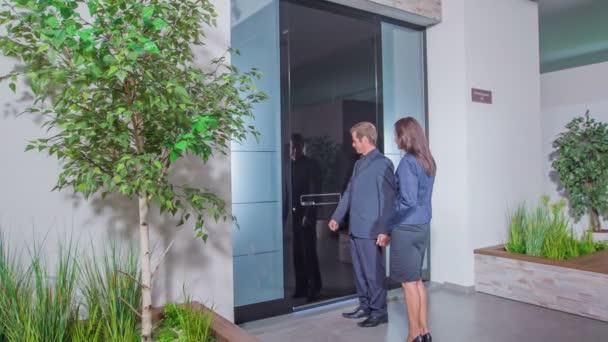 ein Mann öffnet die Tür und er und eine Frau mittleren Alters gehen durch die Tür.