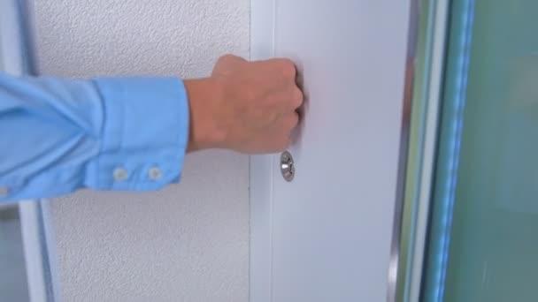 Ein Mann kommt zur Eingangstür und berührt sanft die Oberfläche der Haustür mit der Hand und dann auch den Griff.