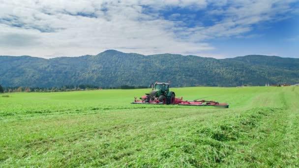 Farmáři mají spoustu práce, když střímají trávu na velké zelené pole. Pole jsou obrovská.