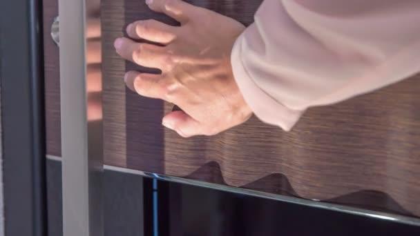 Eine Frau berührt sanft die hölzerne Haustür. der Stil der Tür ist sehr modern.