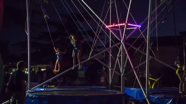 Egy trambulinon ugrálni a vidámparkban.