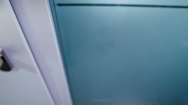 Bílé domovní dveře a držadlo na nich.