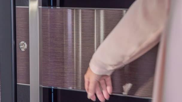 Žena se dotýká vstupních dveří do domu.