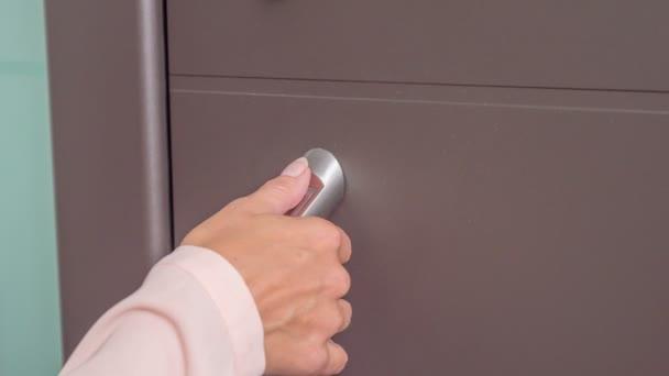 Žena se jemně dotkne kliky na předních dveřích domu..