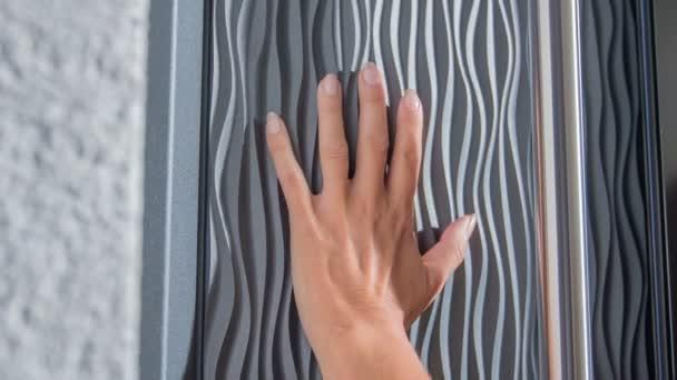 Žena se rukou dotýká velmi moderního stylu předních dveří..