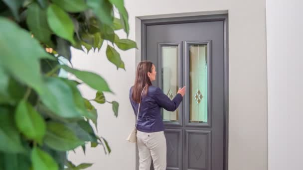 eine Frau, die nach einer neuen Tür sucht, nähert sich einer von ihnen, berührt das Äußere und geht dann hinein.