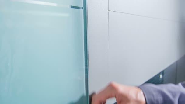 Ein Mann steht vor der Tür und berührt sanft die Haustür mit der Hand.