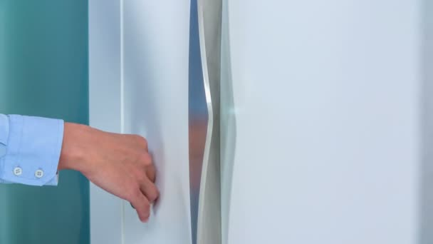 Touching the surface of a white door very gently. The door is very modern and beautiful.