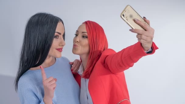 A client and make up artist take a selfie together. Then they check out the photo.