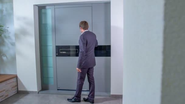 Ein junger Geschäftsmann berührt sanft die graue Oberfläche der Haustür eines Hauses. dann geht er hinein und die Tür schließt sich.