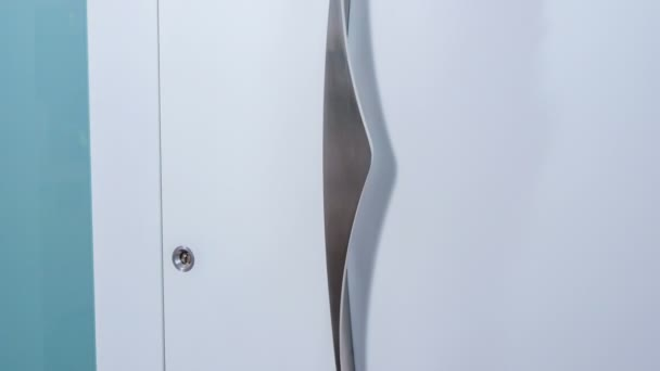Woman touches the handle of the front door. The door is white.