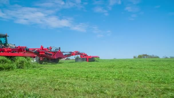 A farmer is sitting on a tractor and the tractor is pulling an agricultural machinery behind it. The machinery is cutting grass.