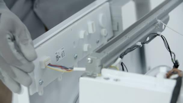 Reparaturarbeiter entfernen die Kunststoff-Frontplatte der Waschmaschine. dann zieht er vorsichtig die Stromkabel ab.