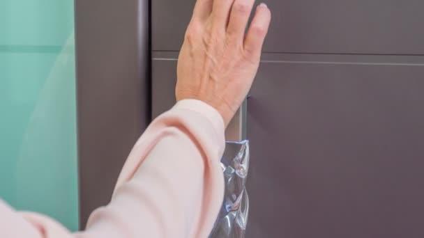 Žena se dotkne velmi speciální rukojeti na předních dveřích.