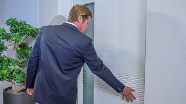 Filmaufnahmen von Geschäftsmann, der Tür in Showroom testet