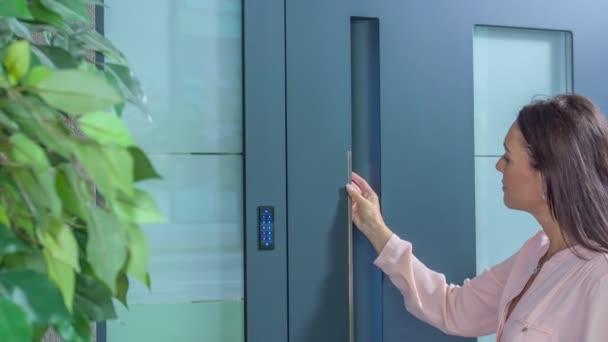 eine Frau drückt einen Code an die Haustür, und dann betritt sie ein Haus.