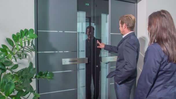 kommt ein Mann und lädt seine Frau ins Haus ein. beide öffnen die Haustür und schließen sie dann.