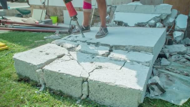 Muž demoluje betonovou zeď silným kladivem na menší kousky. Manželské koleno je obvázané kvůli vážnému zranění.