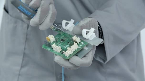 Reparateur in speziellem Mantel trennt sorgfältig elektronischen Schaltkreis, der zur Waschmaschine gehört.