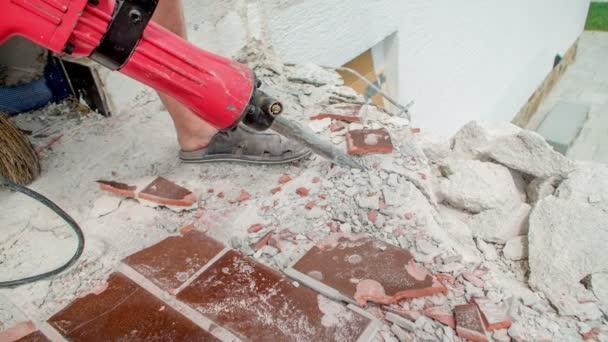 Dělník demolovat betonové konstrukce pokryté tmavě hnědé keramické dlaždice kus po kousku.