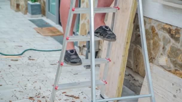 Muž v šortkách a nevhodných botách pomalu sestupuje po žebříku. Okolí je plné odpadků po celém místě.