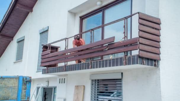 Starší pracovník plný energie se snaží odstranit dřevěnou konstrukci balkónu krumpáčem, ale stavba stojí pevně.